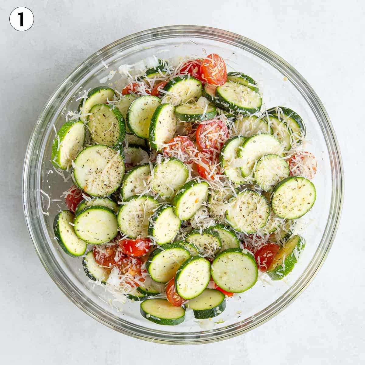 Sliced zucchini, tomatoes, onions, cheese and seasonings in a glass bowl.