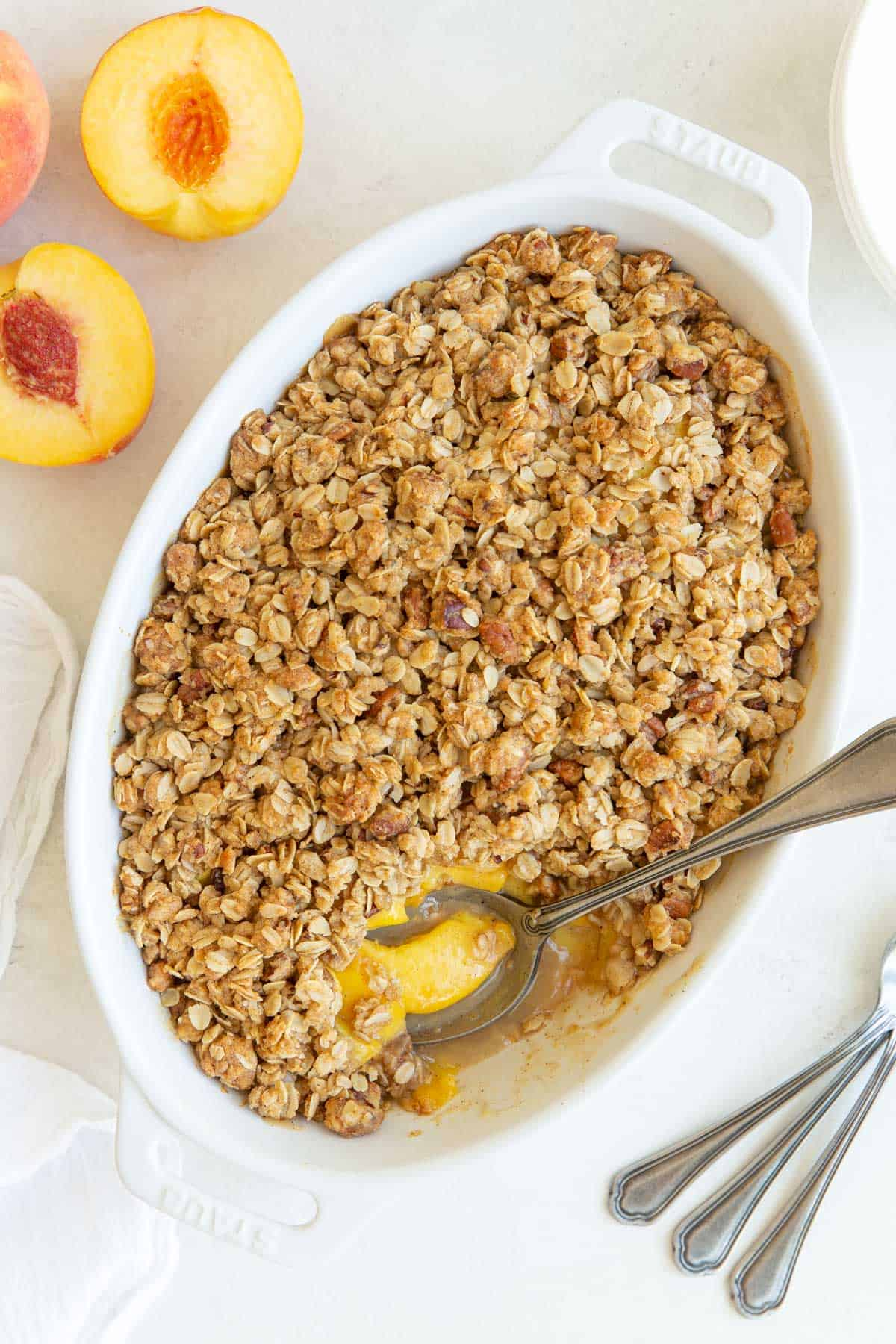 Overhead view of peach crisp in an oval white baking dish with a serving spoon.