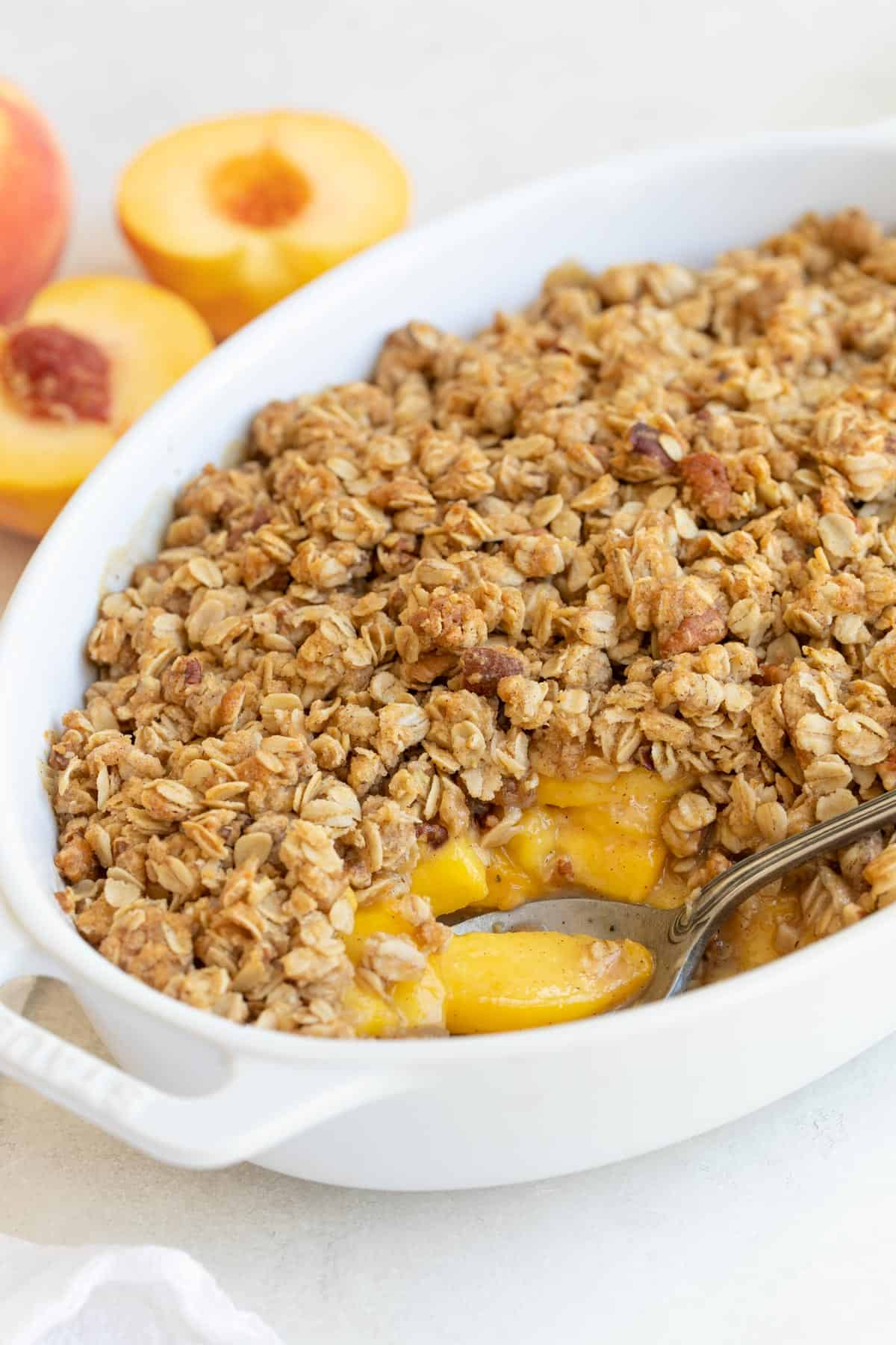 Front closeup view of peach crisp with an oat topping in a white baking dish.