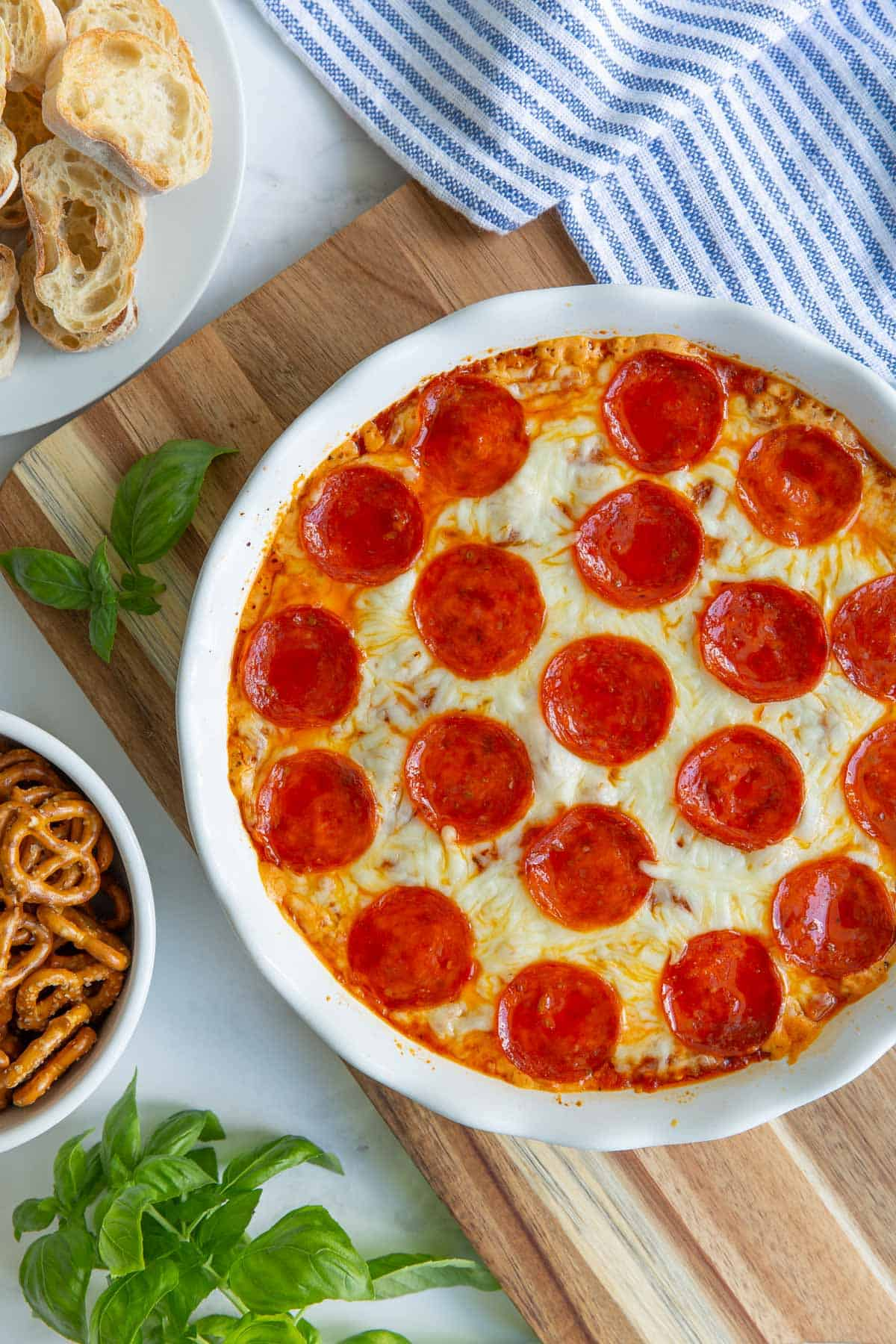 Overhead view of baked pepperoni pizza dip in a white pie dish.