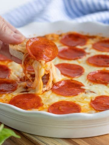 A French baguette slice being dipped into baked pepperoni pizza dip.