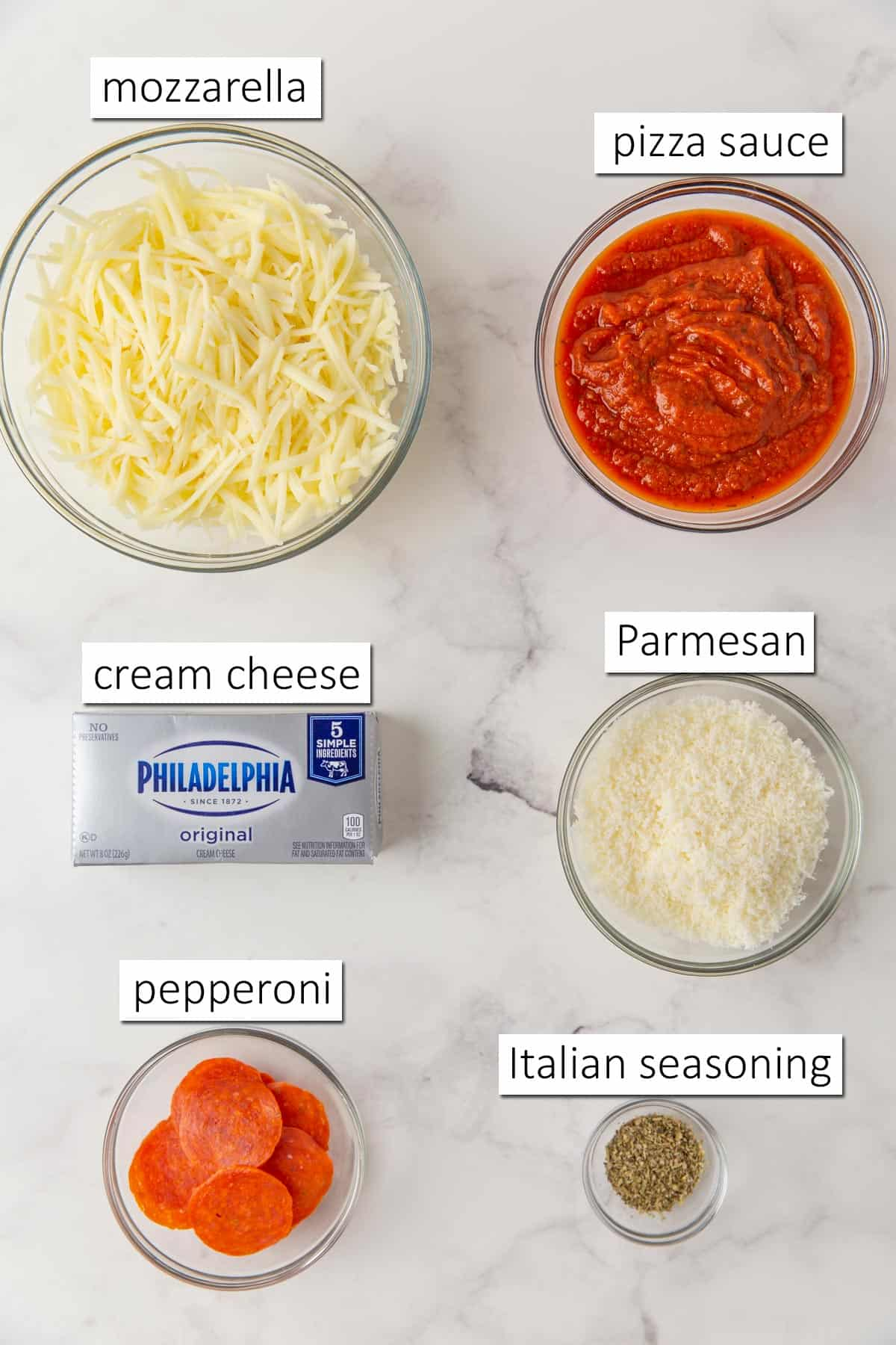 Overhead view of pepperoni pizza dip ingredients on a white marble surface.