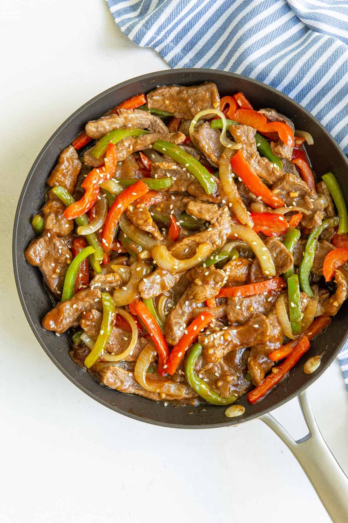 Overhead view of Chinese pepper steak and onions in a skillet by a striped towel.