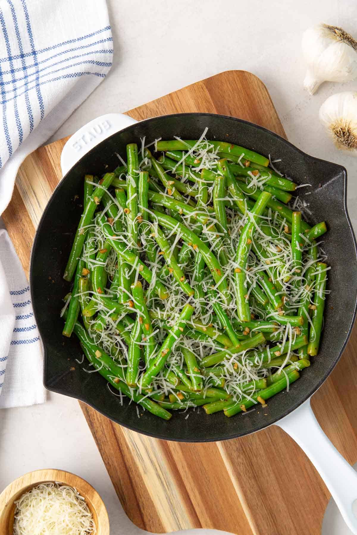 Overhead view of garlic green beans sprinkled with Parmesan in a white skillet.