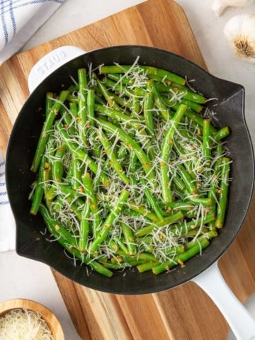 Garlic parmesan green beans in a skillet on a cutting board by a kitchen towel.