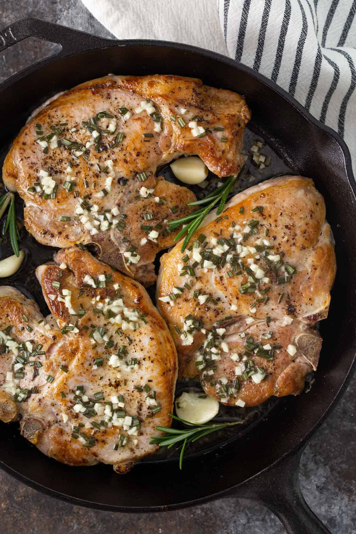 Overhead view of baked garlic and rosemary pork chops in a cast iron skillet.