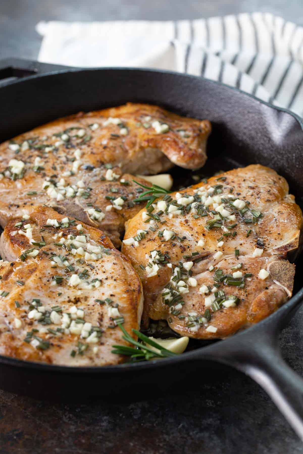 A closeup view of baked pork chops with rosemary and garlic in a skillet.