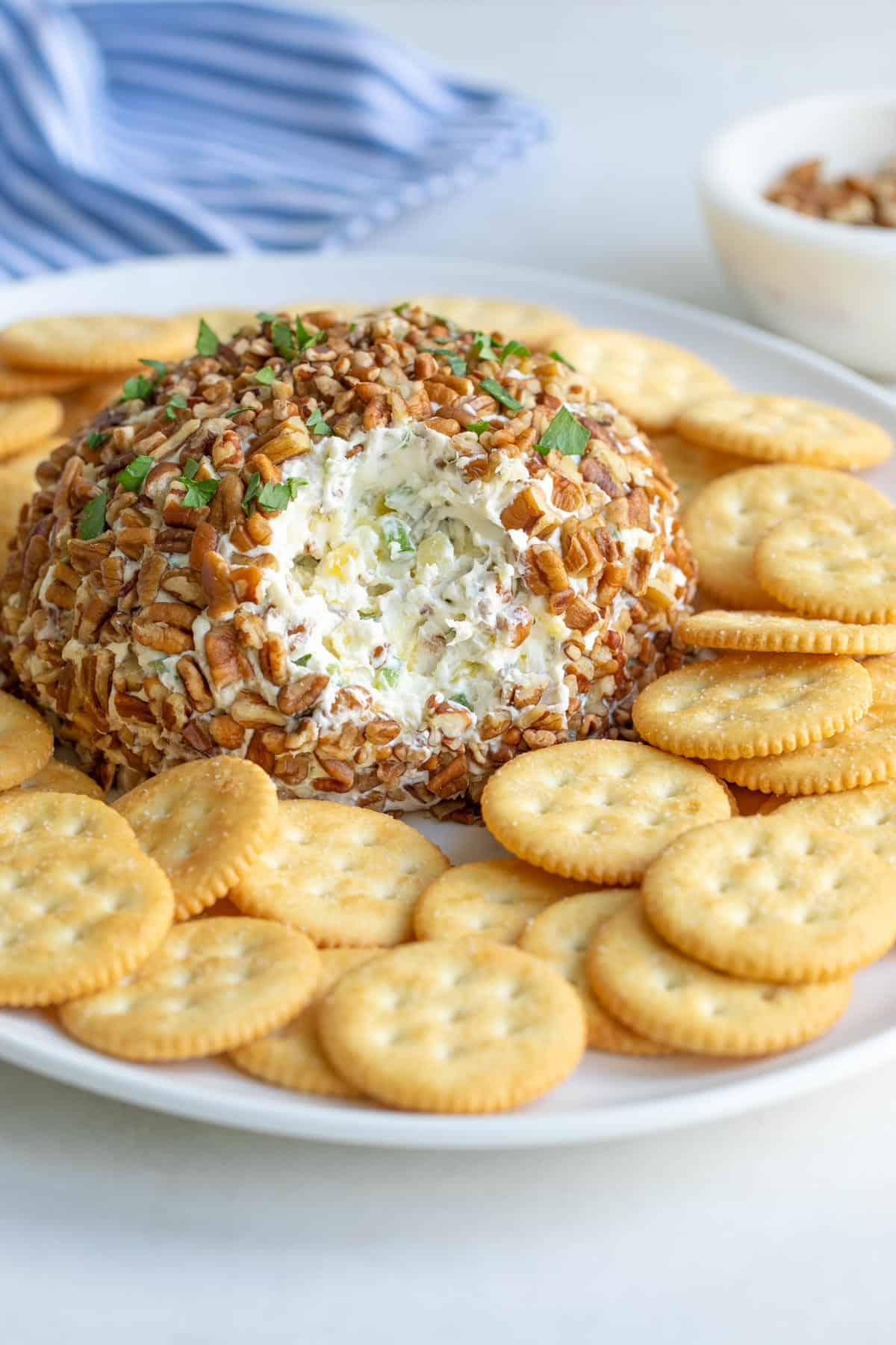 Closeup view of a pineapple cheese ball on a serving platter with crackers.