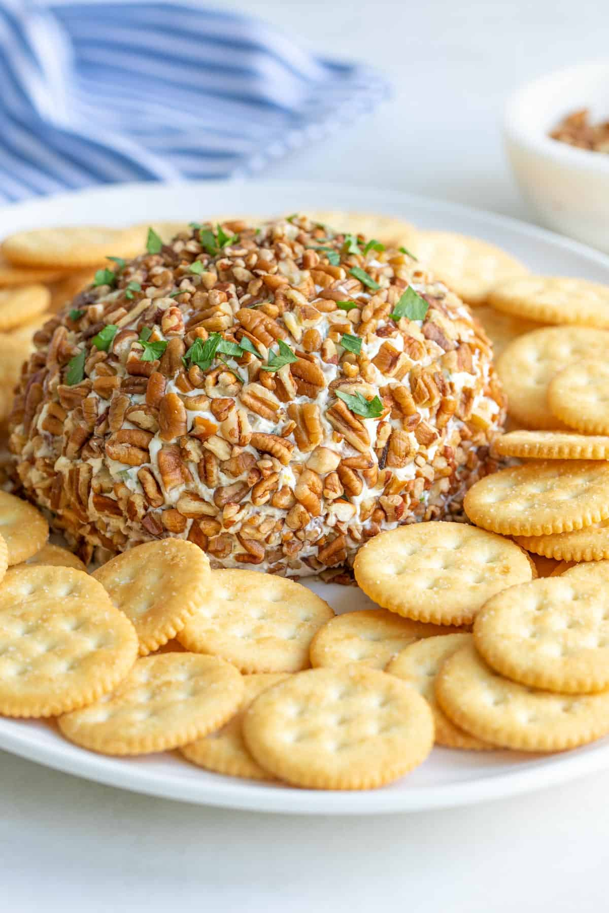 A pineapple cheese ball on a platter with round buttery crackers.