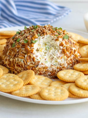 Front view of a pineapple cheese ball on a platter with crackers.