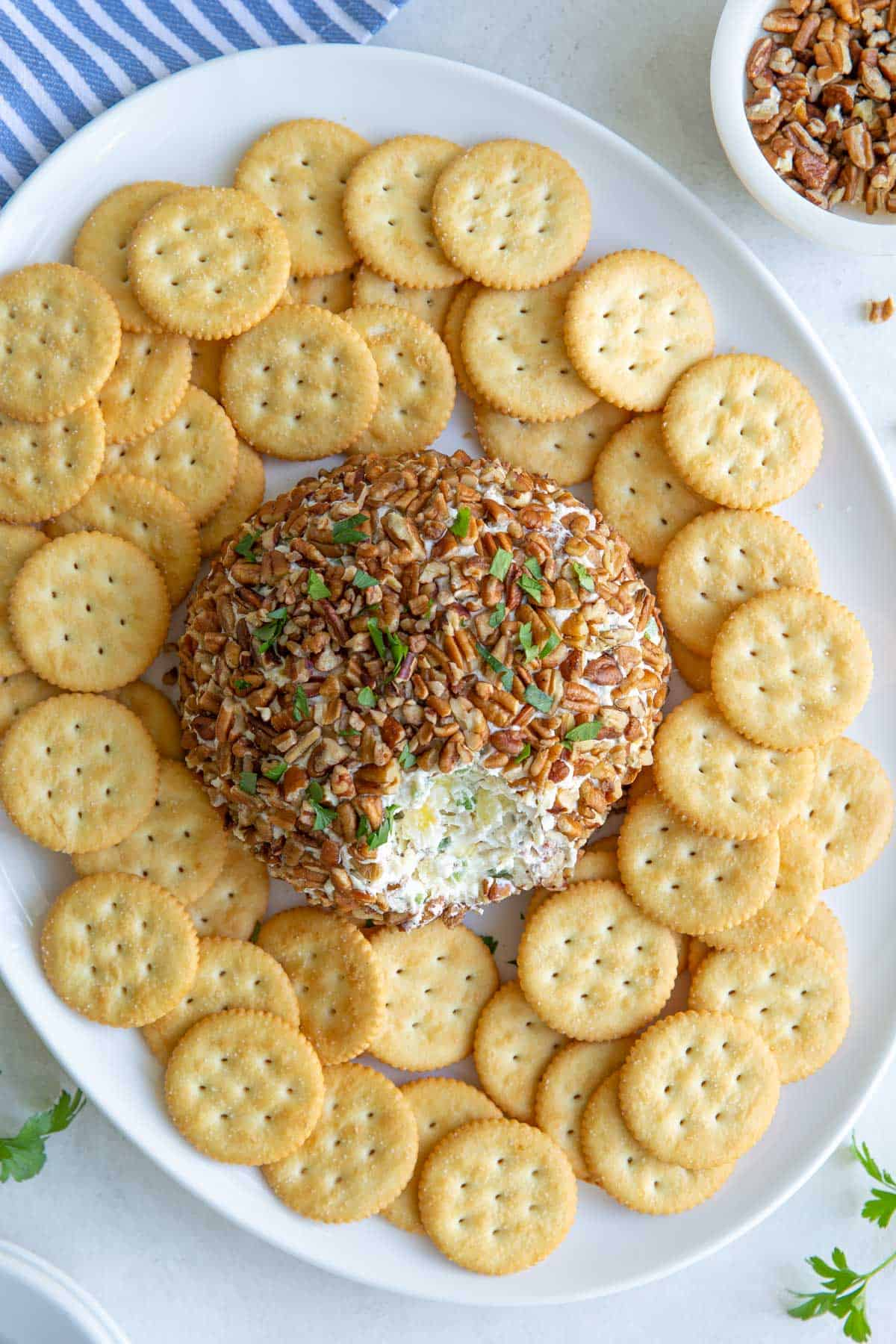 Overhead view of a pineapple cheese ball on an oval white platter with crackers.
